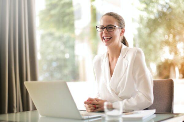 コンピューターの前で笑顔の女性