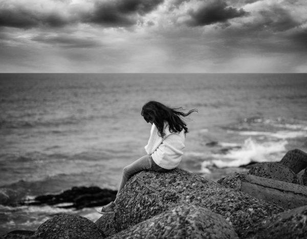 岸辺の岩に座って悩む女性