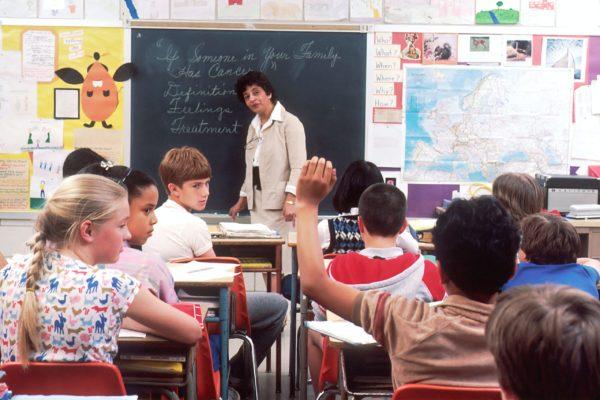 授業中に手を挙げる生徒とそれを見つめる先生
