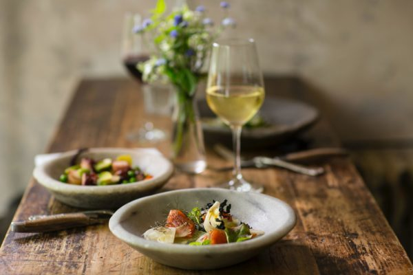 テーブルの上にあるワイングラスと美味しそうな食事