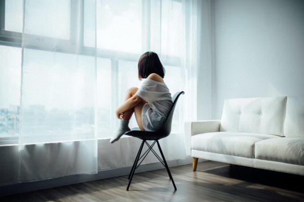 寂しそうに窓から外をぼんやり見る女性