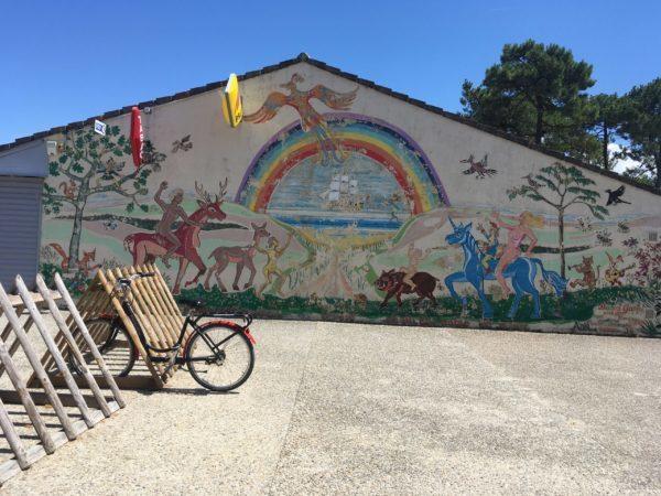 裸の男女がシカやユニコーンに乗っているイラストの壁画