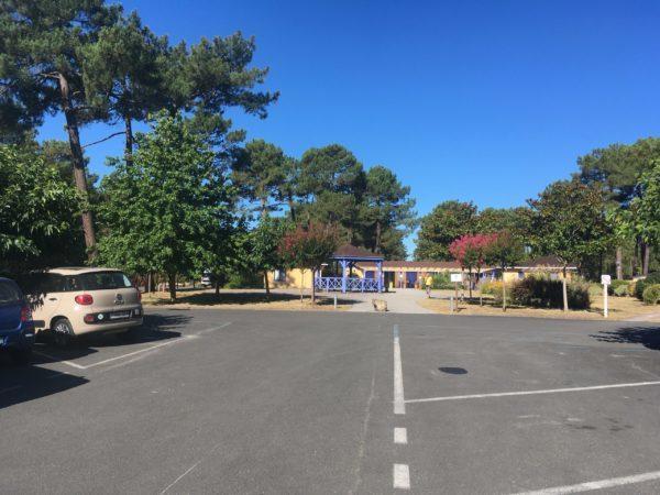 駐車場にとまる車と受付の建物