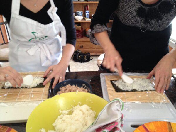 巻き寿司する女性二人の手元