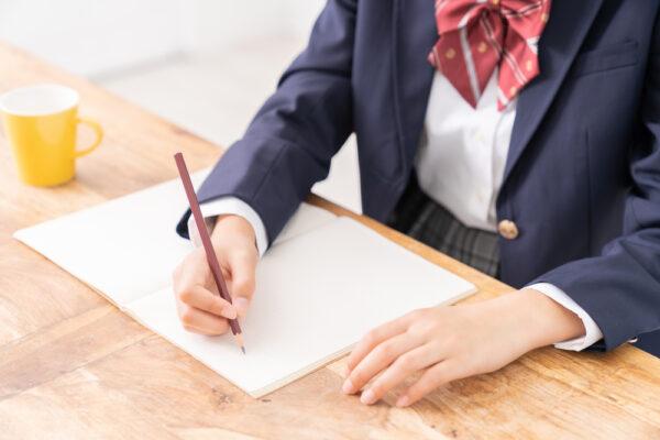 何かを書いている高校生