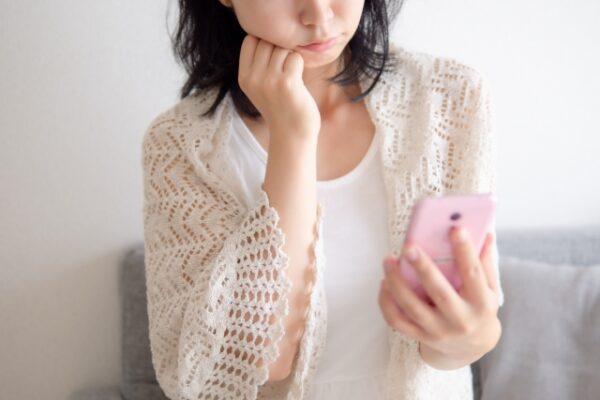 携帯電話片手に悩む女性