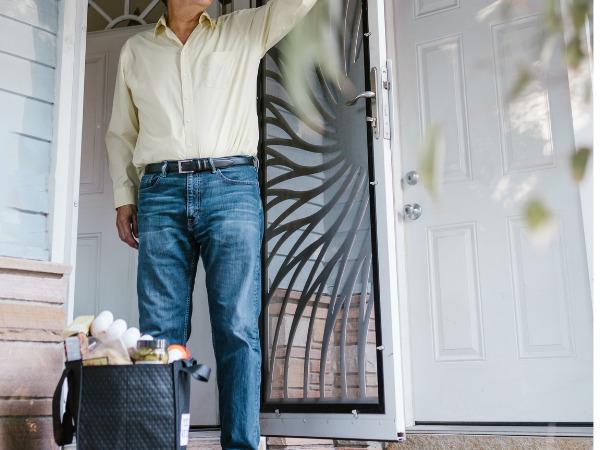 玄関先に配達された食料品と男性