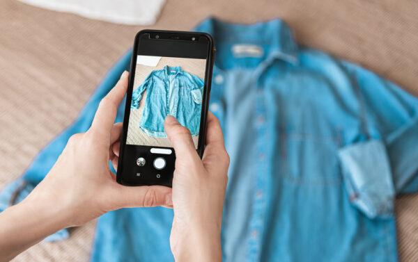 青いシャツの写真を携帯電話でとっている